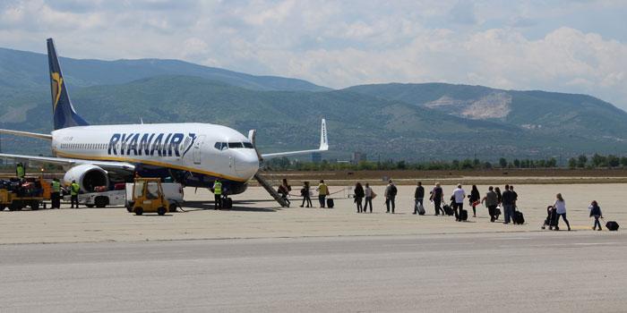 Passagiere steigen mit Handgepäck in Flugzeug ein